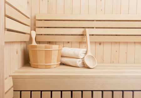 Detail of bucket and white towels in a sauna, wellness and relaxation background photo