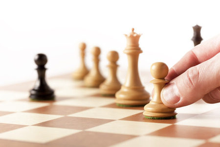 Hand putting a white pawn on a table