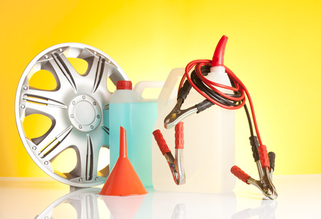 fluids: windshield washer fluids, jump start cables and alloy wheel on yellow background