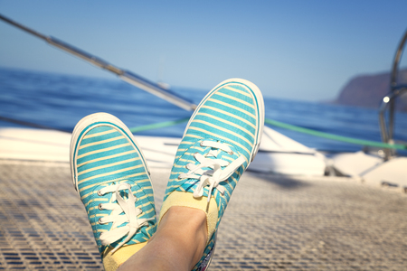 feet crossed: woman lounging on a catamaran sailboat trampoline with her feet crossed.