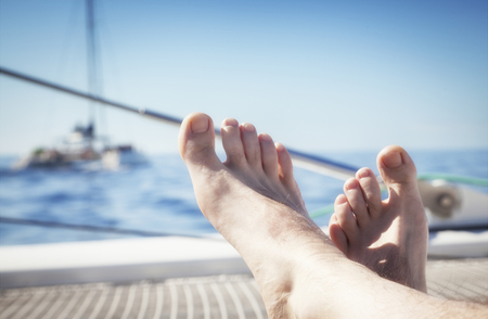 feet crossed: man lounging on a catamaran sailboat trampoline with his feet propped up and crossed.