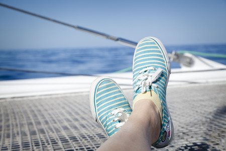 adult cruise: woman lounging on a catamaran sailboat trampoline with her feet propped up and crossed. Stock Photo