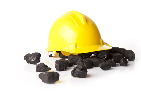 calorific: mining helmet in the background heap of coal