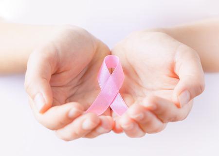 women praying: pink ribbon in hands Stock Photo