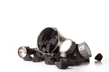 combustible: coal lumps and protective ear muffs isolated on a white background