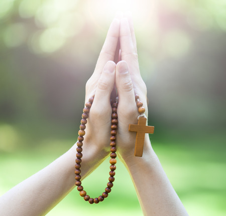 Christian prayer beads in the hand of woman