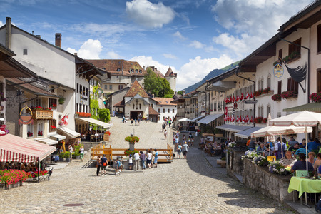 ch: GRUYERES, CH, CIRCA JULY, 2016: View of the main street in the Swiss town of Gruyeres (Switzerland) on a beautiful summer day. Gruyere gives its name to the well-known Gruyere chees