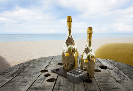 Two bottles of champagne on an old wooden table with pouf seats for romantic dinner for copules honeymoon on a tropical beach