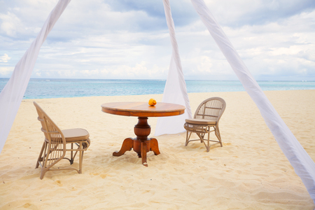 round chairs: Private dining table and wicker chairs for romantic dinner for honeymoon couples on a tropical beach
