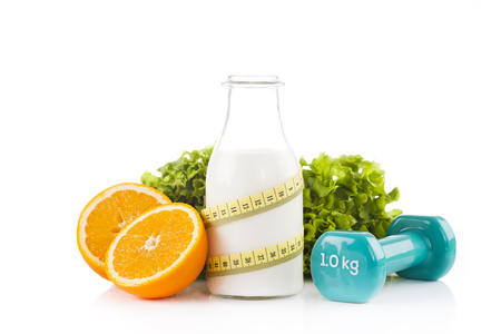 Bottle of protein drinks wrapped with a yellow measuring tape with green lettuce, oranges and blue dumbbels fitness isolated on white