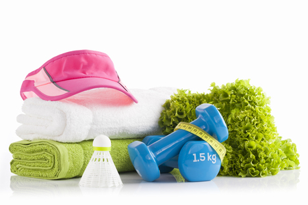 Pink tennis headband cap on a pile of white and green towels with two blue vinyl coated dumbbells wrapped with yellow measuring tape with green lettuce and badminton shuttlecock in the foreground