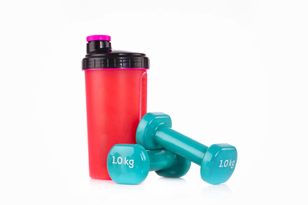 Pink proteins blender bottle with a pair of blue fitness dumbbells. Fitness studio concept. Stock Photo