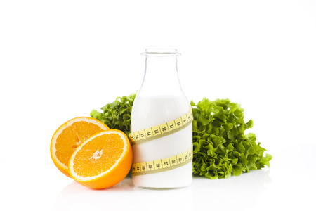 Bottle of protein drinks wrapped with a yellow measuring tape with green lettuce isolated on white