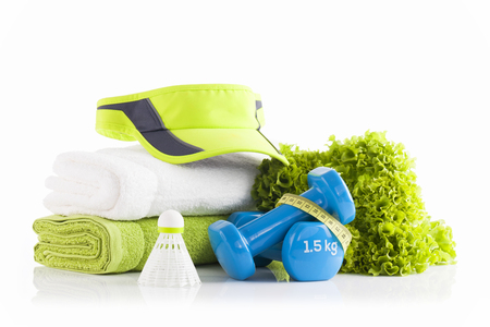 Green tennis headband cap on a pile of white and green towels with two blue vinyl coated dumbbells wrapped with yellow measuring tape. Leaving healthy and fitness concept.