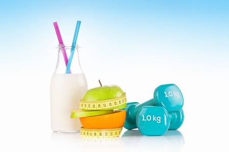 Green apple with measuring tape with a pair of blue fitness dumbbells and a protein drink Stock Photo