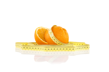 Oranges wrapped with white tape measure. Healthy, organic food and diet concept.