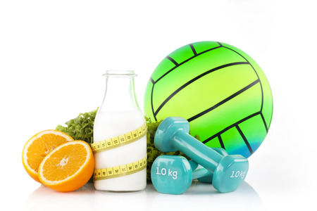 A pair of blue vinyl coated dumbbells with bottle of milk wrapped with a plastic yellow tape measure with two halves of orange with green lettuce and green rubber handball in the background