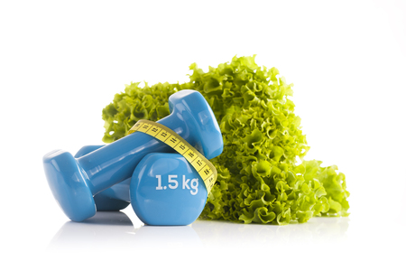 A pair of blue fitness dumbbells wrapped with a yellow tape measure and bottle of protein drink with green lettuce in the background Stock Photo
