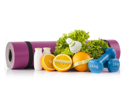 A pink yoga mat Pilates and leaning against green lettuce with, a pair of blue fitness dumbbells and oranges in the foreground. Fitness and Pilates concept