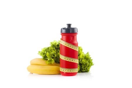 A red bicycle water bottle wrapped with a plastic yellow measuring tape with green lettuce in the white background Stock Photo