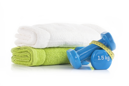 Pile of white and green towels with two blue vinyl coated dumbbells wrapped with yellow measuring tape. Leaving healthy and fitness concept.