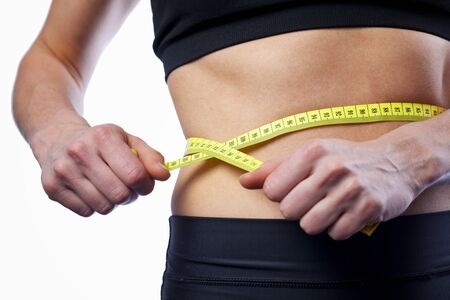 boxing tape: Female athlete measuring waist, checking results of active workouts Stock Photo