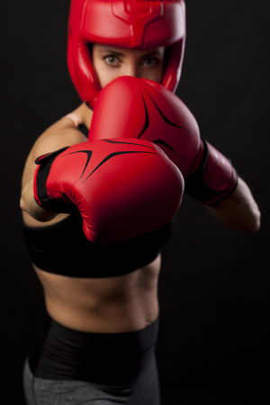 Female boxer punching with red boxing gloves