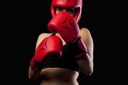 hitting: Female boxer punching with red boxing gloves