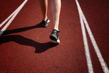 Runner feet running on racetrack closeup on shoe Stock Photo