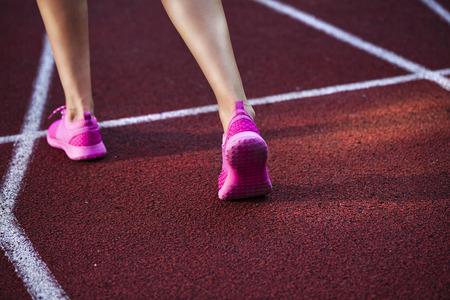 Runner feet running on racetrack closeup on shoe.