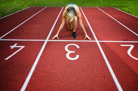 Female Hands on starting line waiting for start in running track Stock Photo