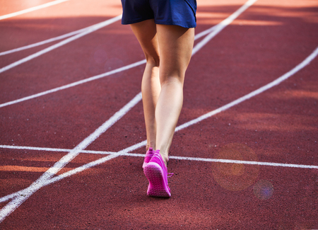 Close up on beautiful female legs with pink shoes on the running track