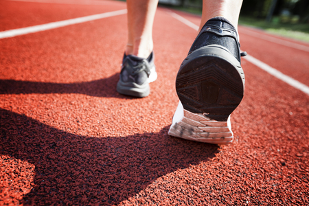 Runner feet running on racetrack closeup on shoe. Woman fitness jog workout welness concept. Stock Photo