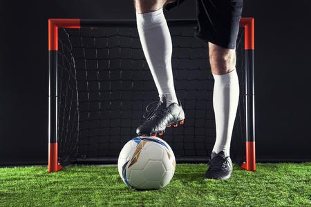 Soccer  striker dribbling in front of the goal