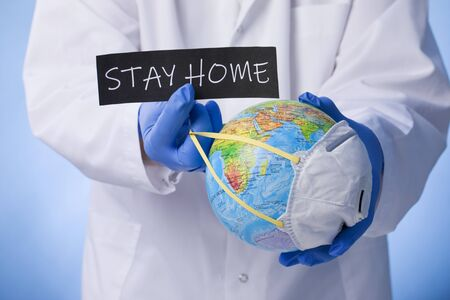Medical officer holding sign of Stay at home with planet earth wearing mask Stock Photo