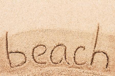 swimm: Word Beach handwritten on sand of beach  Stock Photo