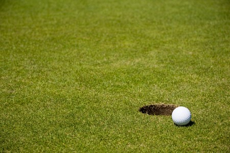 Golf ball very close to a hole on a putting green photo
