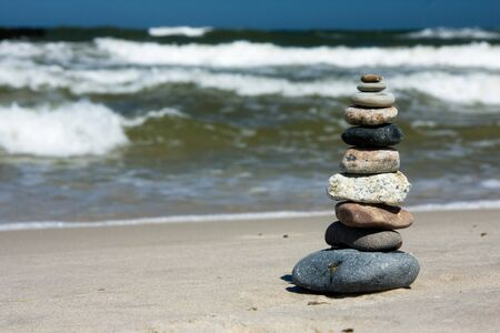 Ten differently sized and colored pebbles, stacked on a beach over a sea