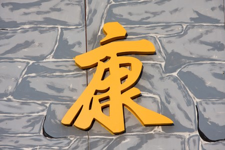 Yellow chinese symbol on an artificial brick wall photo