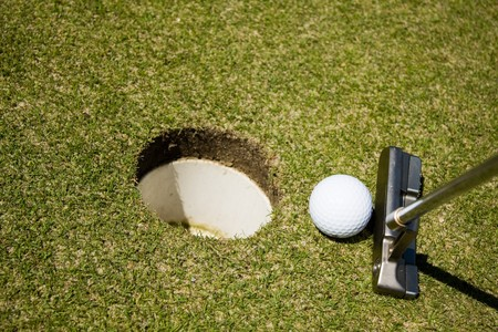 Putting golf ball to a hole on green grass photo