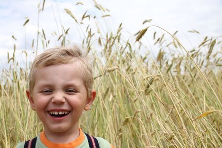3 years old boy laughting on a wheat field photo