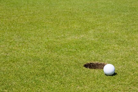 Golf ball very close to a hole on a putting green. Deep depth of field. photo