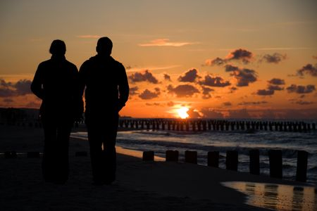 Silhouette of couple taking a walk on beach in sunset photo
