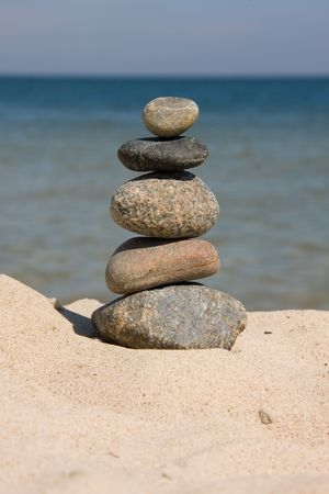 differently: Six differently colored and sized pebbles stacked on a beach Stock Photo