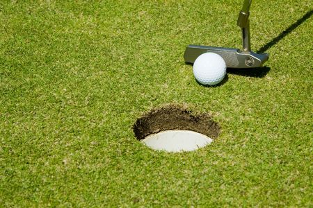 Putting golf ball to hole on a putting green photo