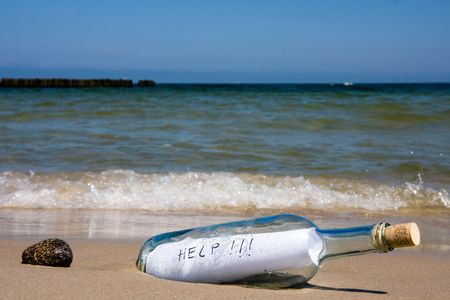 castaway: Close-up of help message in bottle on a sea shore Stock Photo