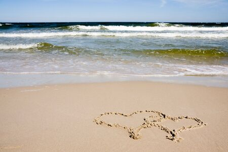 Two hearts drawn on a sandy beach in sunny day photo