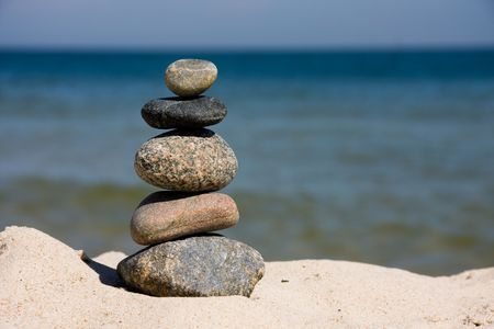 differently: Five differently colored and shaped pebbles stacked on a beach Stock Photo