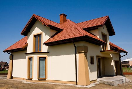 Incompleted single family small yellow house against blue sky Stock Photo - 5081367