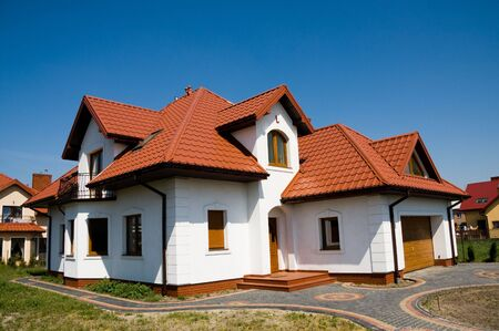 Single family small white house against blue sky photo